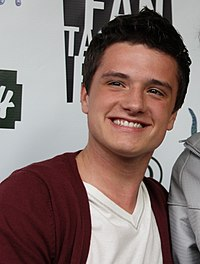 Josh Hutcherson smiling for a picture wearing casual clothing.