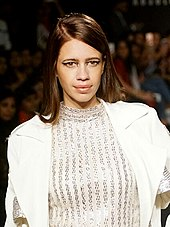 Koechlin posing for the camera in a white coat and a sheer dress.