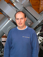 Half-length portrait of a man with descending brown hair. He is standing, looking into the camera and smiling. He is wearing a blue sweatshirt. A part of an astronomical telescope is visible in the background.