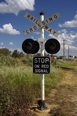 Grade crossing signals - Warning device in Australia, with crossbuck and flashing lights.