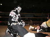 A masked wrestler wearing a full body suit that makes him look like a skeleton/