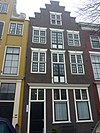 foto van Pakhuis met trapgevel, bovenvensters strekken met maskersluitstenen, pui gewijzigd. Kruisvensters