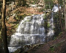 A waterfall spills down a sunlit stone wall made of many layers of rock, surrounded by foliage.