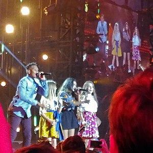 Les Kids United. Erza est à droite, en jupe rose.