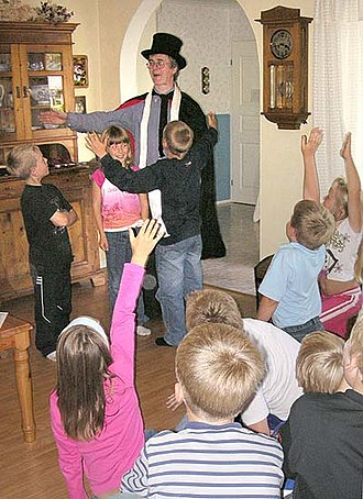 "Children's magic - An amateur magician performing ""children's magic"" for a birthday party audience."