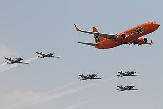 Africa Aerospace and Defence Expo - A Mango Airlines 737 flies in formation with the South African Air Force Silver Falcons aerobatic team at AAD 2014