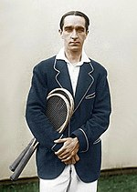 A man in a sports jacket holding two rackets