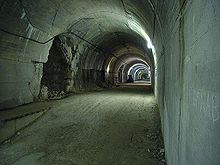 A long view down a lit gravel—paved concrete tunnel which has a series of openings on the left hand side
