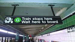 "An overhead sign at an underground ""G"" train station. The sign's text says, ""'G' train stops here. Wait here to board"". There is an icon of a train on the left side of the sign, next to the text."
