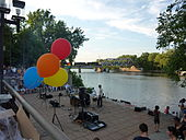Band playing in the mid-distance, bright balloons in the foreground