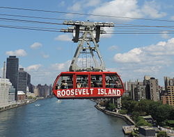 A red-colored tram going over a river