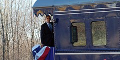 Obama is standing aboard the back platform of a train and looking to the side of the train. There is a red, white and blue banner hanging over the rear railing.