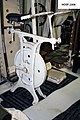Painted iron frame stationary exercise bicycle; White; black leather seat mounted above iron wheel rotated by 2 foot pedals (9de4b9c4-fcdd-40e5-b3a7-64486589d364).jpg