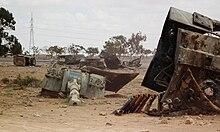 Biter av en ødelagt tank, særlig kanontårnet, ligger i et sandlandskap.