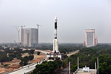 Panoramic view of GSLV-F08 on the Mobile Launch Pedestal with the Vehicle Assembly Building in the background.jpg