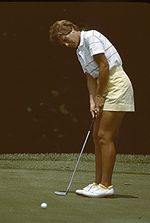 A blonde-haired woman in a mostly white shirt and yellow shorts is hitting a putt with a putter with white golfing shoes on