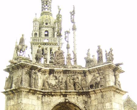 "View of the south face. In the buttress to the left we see the Annunciation. On the corniche and from left to right we see the visitation, the nativity, the visit of the three wise men and the flight into Egypt. On the buttress to the right we see Jesus in discussion with two lawyers in the temple. On the left of the platform we see two horsed and one standing soldier, the descent into the mouth of Hell, another horsed soldier, a Jew carrying details of the accusation being leveled at Jesus and a soldier putting the ""royal"" robe on Jesus."