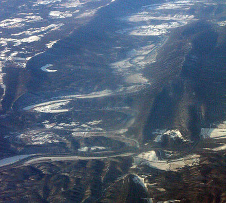 Oblique air photo of the confluence of the North and South Branches near Green Spring, West Virginia. Facing southwest. River Mountain is on the right, and Town Hill is on the left. Potomac North Branch South Branch confluence air.jpg