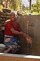 Prem Kumari Budhathoki washing her hands at the tapstand, Tanmang, Parbat, Nepal (10714496795).jpg