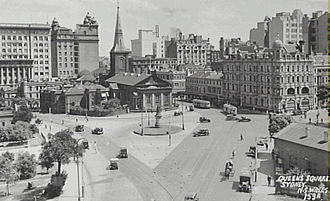 Aerial black and white photo of the junction of Macquarie and King Streets when traffic could still run from one into the other. Buses and other vehicles are on the roads and the now demolished building at the corner can be seen