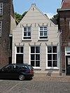 foto van Huis met gebosseerd witgepleisterde topgevel en stoep van gele steentjes