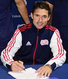 Revolution's coach Jay Heaps signs a document of support with the U.S. Coast Guard.jpg