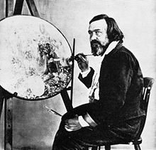 Photograph of a bearded, middle-aged man. He is seated and holding a paint brush. In front of him is an unfinished, circular painting on an artist's easel.