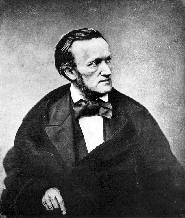A photograph of the upper half of a man of about fifty viewed from his front right. He wears a cravat and frock coat. He has long sideburns and his dark hair is receding at the temples.