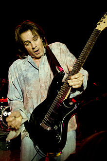 A fifty-five-year-old man is holding an electric guitar in his left hand more than mid-way down its neck. His right hand has a plectrum between thumb and forefinger, it is poised above and to the left of the guitar. The man has dark hair and is open mouthed while looking down at the guitar. Behind him is an obscured drum stand and other band equipment.