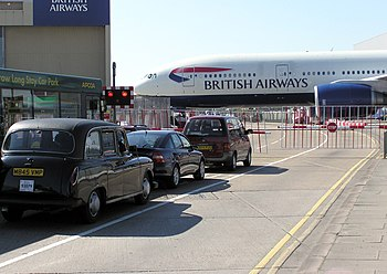 An unusual road at London Heathrow Airport, England. A British Airways Boeing 777-200 is being towed across a public road on its way to the maintenance hangars.
