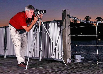 A photographer using a tripod for greater stability during long exposure. - Photography