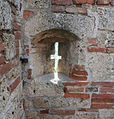 Rocca di Arquta del Tronto - feritoia cruciforme sulla merlatura ad angolo del mastio.jpg