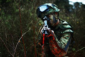 SAR 21 - A Singaporean soldier takes aim with the SAR-21. Note the emitted red laser beam.
