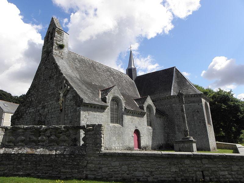Église Saint-Caradec de Saint-Caradec-Trégomel (56). Façade occidentale et flanc sud. Au premier plan: baie de l'ancien ossuaire réemployée en ballustrade. A droite: croix de cimetière.