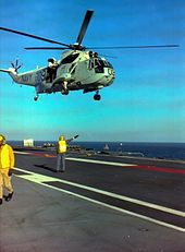 A helicopter hovering over the flight deck of a ship. Two men in fluorescent yellow vests are visible; one is using hand signals to direct the helicopter, the other is walking out of frame.