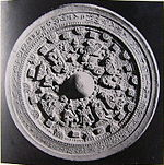 A round object with an inscription in Chinese characters around the outer part and figurative relief in the middle.