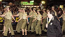 Colour photo of men and women marching down a street while wearing green military uniforms