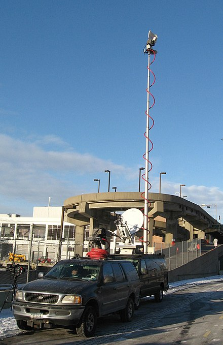 TV news production truck doing a remote broadcast at New York Passenger Ship Terminal. The tall telescoping antenna is pointed at a receiving antenna on the Empire State Building, allowing the truck to send video by microwave link to the production facility. TV remote pickup Pier 88 jeh.JPG