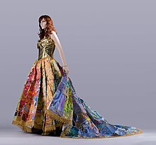 A mannequin wears a multicolored gown with a golden bodice, full skirt, and flowing train.
