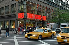 "A street view of a store front prominently features a yellow taxi in front of the store. The walls contain clear windows with the phrase ""Tower Records - Video"" in bright orange lights."