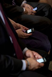 three people in dark suits thumbtyping on BlackBerry's while seated