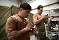 U.S. Navy Boatswain's Mate 1st Class Eddie Montalvo, left, and Mineman 1st Class Thomas Harrell, both assigned to Commander, Task Force (CTF) 56, clean M4 carbine bolt assemblies during weapons training at Naval 140212-N-OU681-157.jpg