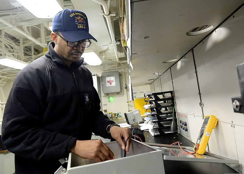 6cd9639a File:U.S. Navy Interior Communications Electrician 2nd Class Allen Trent,  assigned to the amphibious assault ship USS America (LHA 6) ...