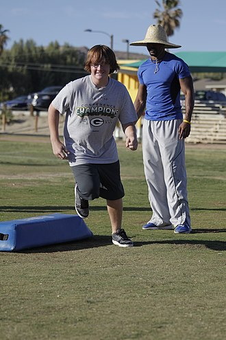Kareem Larrimore - Kareem Larrimore watches as a young participant runs an agility drill during a three day football camp