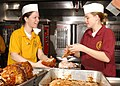 US Navy 021103-N-1159M-001 Mess Management Specialist 3rd Class Nicole Phillipe (left) and Mess Management Specialist Seaman Crista Spencer, prepare roast turkey for the noontime meal aboard the ship.jpg