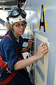 US Navy 040514-N-4757S-009 Quartermaster 2nd Class Jessica Pulido prepares to paint the Battle Efficiency E Award on the side of the island aboard the aircraft carrier USS Harry S. Truman (CVN 75).jpg