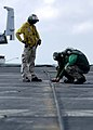 US Navy 050112-N-0057P-075 Flight deck Personnel make quick adjustments to the number three arresting wire on the flight deck aboard the Nimitz-class aircraft carrier USS Abraham Lincoln (CVN 72).jpg