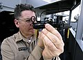 US Navy 060403-N-7981E-085 Senior Chief Quartermaster John Trail demonstrates the use of a stadimeter, a navigational instrument used to determine the distance from one object to another.jpg