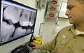US Navy 061216-N-5345W-018 General dentistry officer Lt. Adam Clock looks over x-rays while taking care of a patient in the dental lab aboard the Nimitz-class aircraft carrier USS Harry S. Truman (CVN 75).jpg