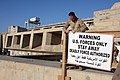 US Navy 081203-M-9943H-015 U.S. Marine Sgt. Tyler Ackermann, assigned to Headquarters Company, Regimental Combat Team 5, takes down a warning sign at the Haditha Dam in Anbar Province, Iraq.jpg